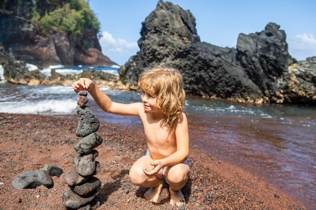 Kind mit zen-steinen am meeresstrand, meditation, spa und harmonie. ruhiges gleichgewichtskonzept. kinder spielen am strand.