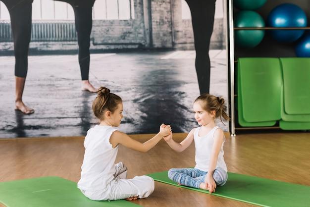 Kind mit zwei mädchen, das auf yogamatte sitzt und in der turnhalle spielt