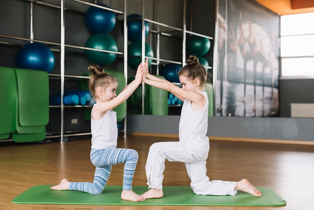 Kind mit zwei mädchen, das zusammen an der turnhalle trainiert