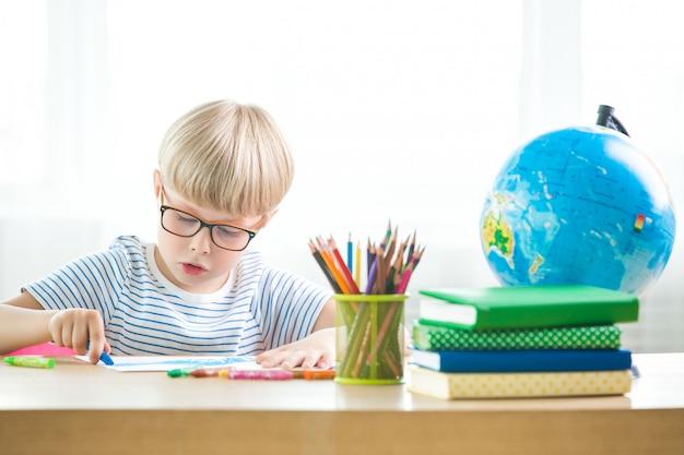 Kind müde zu lernen. unglücklicher schüler. erschöpfter kleiner schuljunge. junge im klassenzimmer. kind macht hausaufgaben.