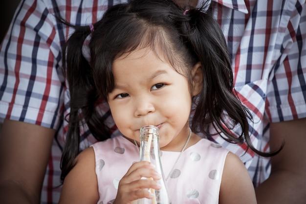 Kind nettes kleines mädchen sitzt auf ihrem vater und trinkt aus einer flasche