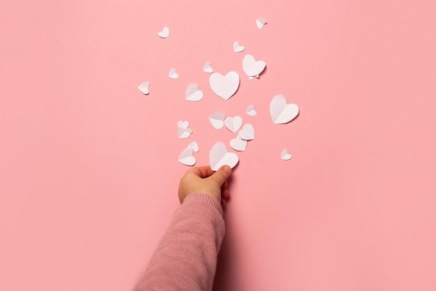 Kind nimmt eine valentinskarte vom papier auf einem rosa hintergrund. zusammensetzung valentinstag. banner. flache lage, draufsicht.