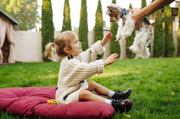 Kind nimmt in den händen lustigen hund im garten, beste freunde. kind mit welpen, der auf dem rasen auf hinterhof sitzt. glückliche kindheit