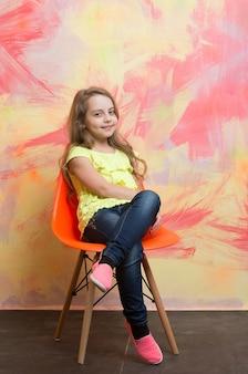 Kind oder kleines lächelndes mädchen, das auf orangefarbenem stuhl auf buntem abstraktem hintergrund in jeans und t-shirt mit langen blonden haaren sitzt
