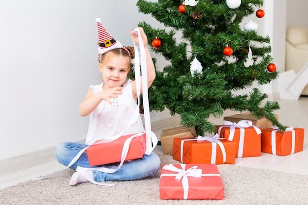 Kind öffnet weihnachtsgeschenke. kind unter weihnachtsbaum mit geschenkboxen.