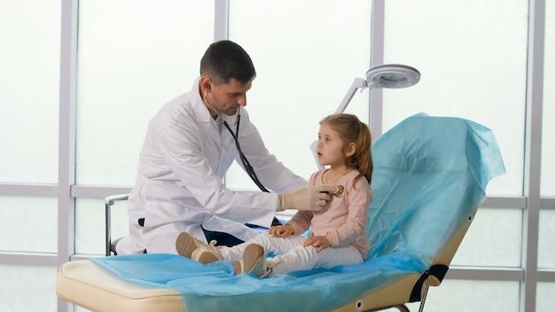 Kind patient besucht die arztpraxis. der arzt hört mit einem stethoskop auf die lunge des kindes, spricht liebevoll mit dem kleinen mädchen. angenehmer aufenthalt des kindes in der klinik.