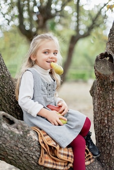 Kind pflückt äpfel auf bauernhof im herbst. kleines mädchen, das im apfelbaumobstgarten spielt. gesunde ernährung.