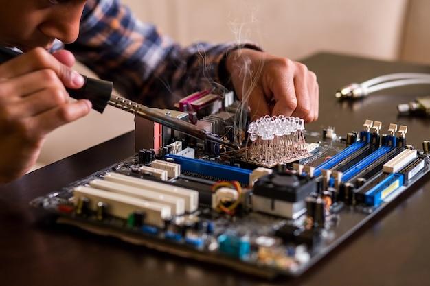 Kind repariert motherboard auf tisch.