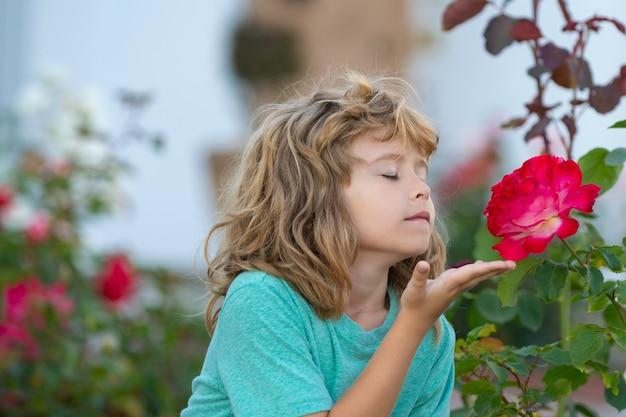 Kind riechende blume. kinder lustiges gesicht. süßes kind genießt die natürliche umgebung durch outdoor-aktivitäten wie spielen, berühren und riechen von rose.