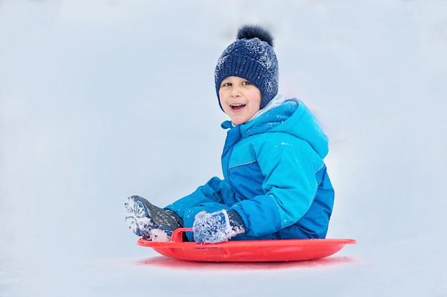 Kind rollt einen schneehügel hinunter. junge, der hinunter schneehügel im winter schiebt.