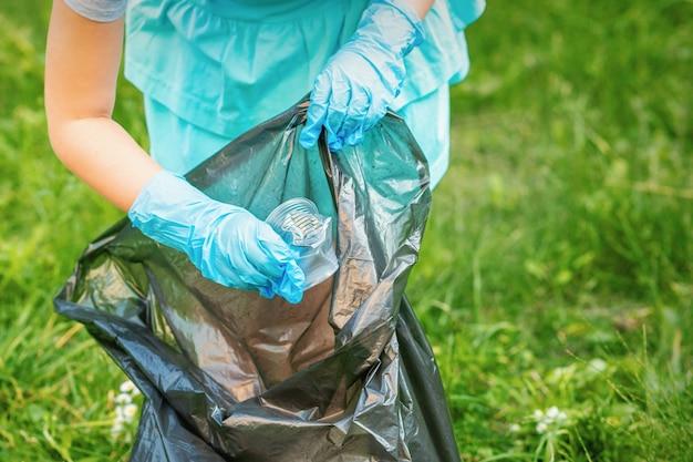 Kind sammelt plastikmüll vom gras, das müll in müllsack im park wirft