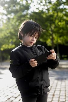 Kind schaut sich im park etwas auf dem handy an