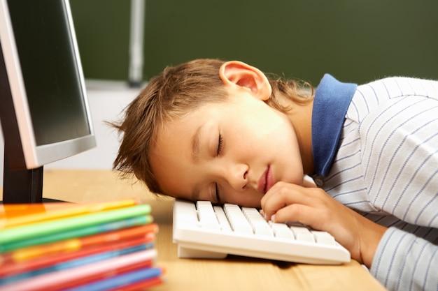 Kind schläft auf computer-tastatur
