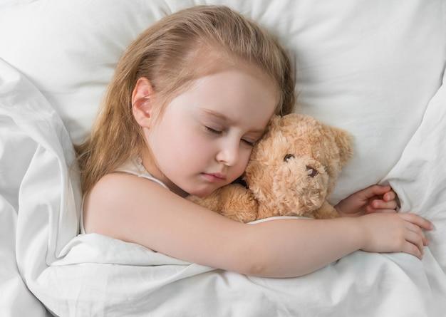Kind schläft mit einem süßen teddybär