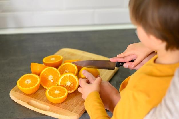 Kind schneidet orangen in zwei hälften