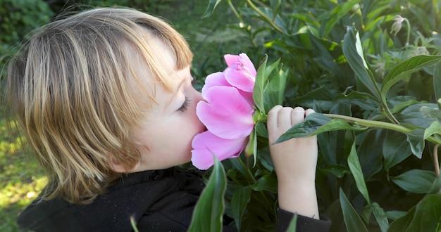 Kind schnüffelt eine blume