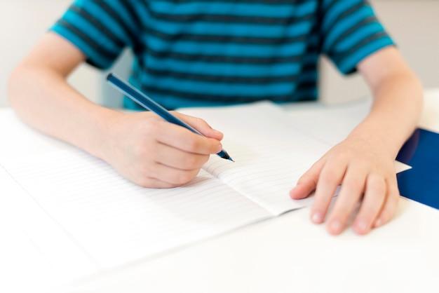 Kind schreibt auf ein leeres notizbuch