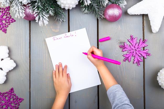 Kind schreibt den brief an den weihnachtsmann. kid hände. ansicht von oben.