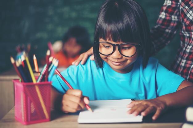 Kind schreibt ein buch in den klassenraum.