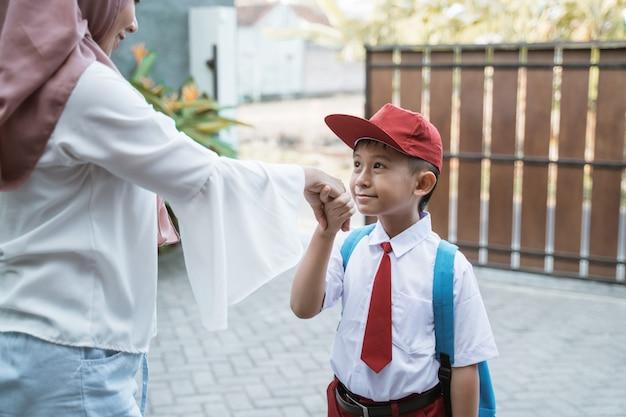 Kind schüttelt hand und küsst hand vor der schule