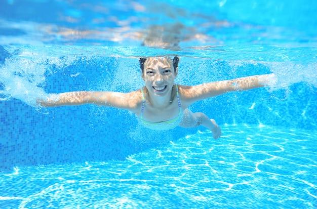 Kind schwimmt im pool unter wasser, glückliches aktives mädchen hat spaß unter wasser, kindersport im familienurlaub