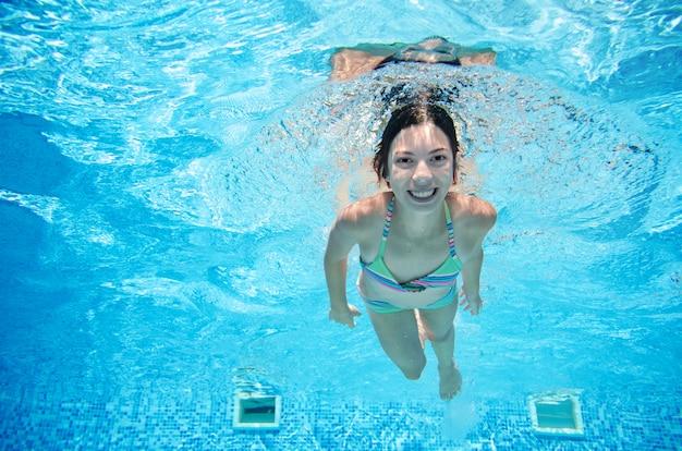 Kind schwimmt im pool unter wasser, glückliches aktives mädchen in den schutzbrillen hat spaß im wasser, kindersport auf familienurlaub