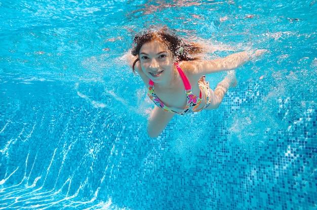 Kind schwimmt im pool unter wasser, glückliches aktives mädchen taucht und hat spaß im wasser, kindereignung und sport auf familienferien