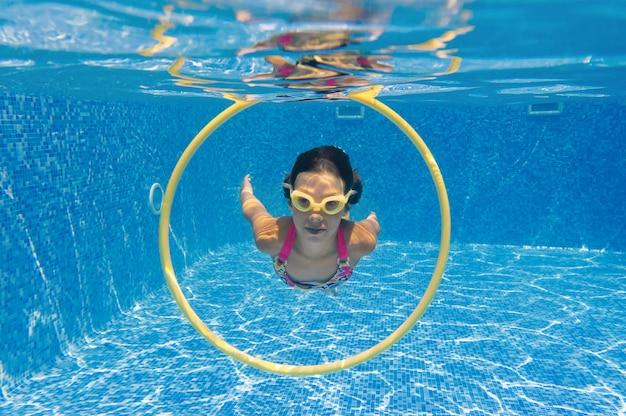 Kind schwimmt im pool unter wasser, glückliches aktives mädchen taucht und hat spaß unter wasser, kindersport im familienurlaub
