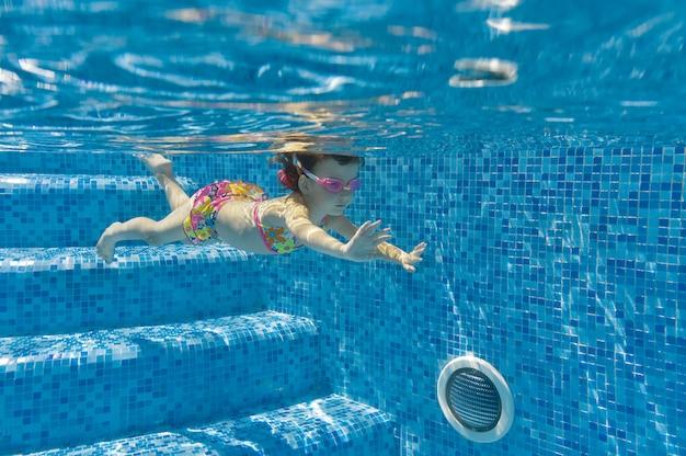 Kind schwimmt im pool unter wasser
