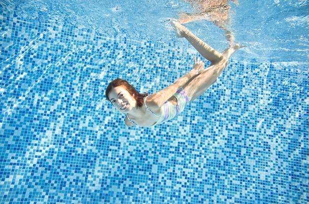 Kind schwimmt im schwimmbad unter wasser glückliches aktives mädchen springt tauchgänge und hat spaß unter wasser