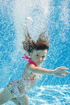 Kind schwimmt im schwimmbad unter wasser kleines mädchen springt tauchgänge und hat spaß unter wasser
