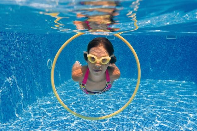 Kind schwimmt im swimmingpool unter wasser, glückliches aktives mädchen taucht und hat spaß unter wasser, kindereignung und sport auf familienurlaub auf erholungsort