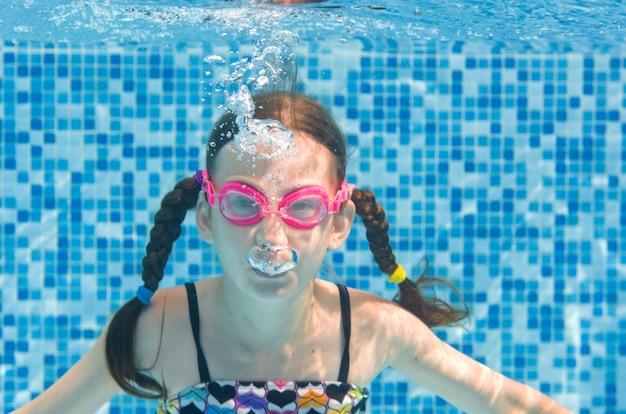 Kind schwimmt unter wasser im schwimmbad, glückliches aktives mädchen in der schutzbrille taucht und hat spaß unter wasser, kinderfitness und sport im familienurlaub im resort