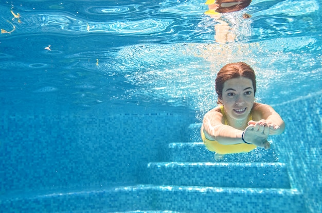 Kind schwimmt unter wasser im schwimmbad, glückliches aktives teenager-mädchen taucht und hat spaß unter wasser, kinderfitness und sport im familienurlaub im resort
