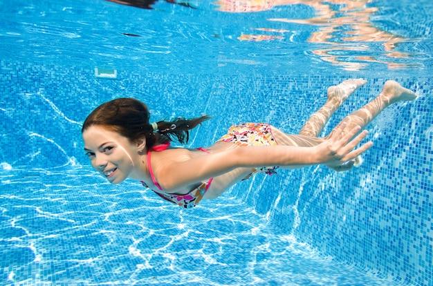 Kind schwimmt unter wasser im schwimmbad kleines aktives mädchen taucht und hat spaß unter wasser