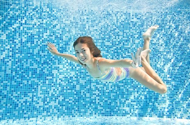 Kind schwimmt unter wasser im schwimmbad