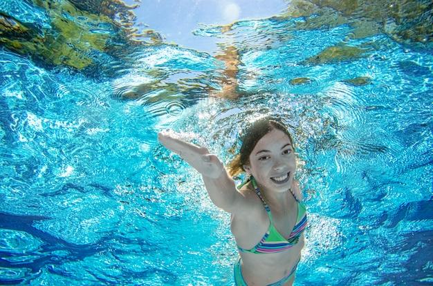 Kind schwimmt unter wasser im swimmingpool, glückliches aktives jugendlichmädchen taucht und hat spaß unter wasser, kindereignung und sport auf familienurlaub auf erholungsort