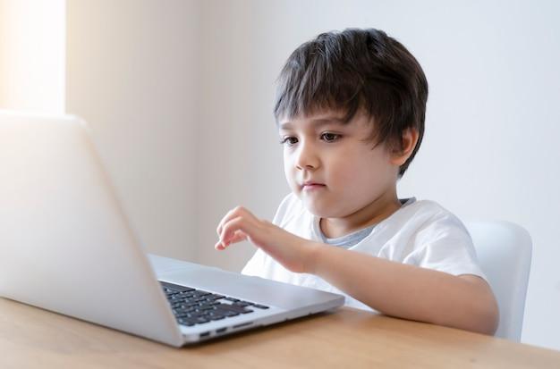 Kind selbstisolation mit tablet für seine hausaufgaben, kind mit digitalen tablet-suchinformationen im internet