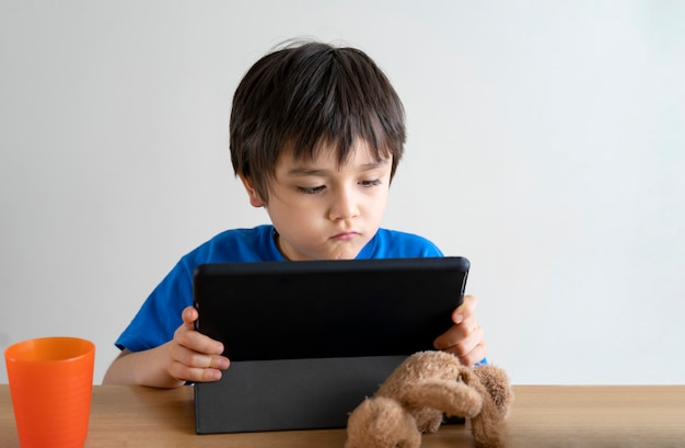 Kind selbstisolation mit tablet für seine hausaufgaben oder online-unterricht lernen