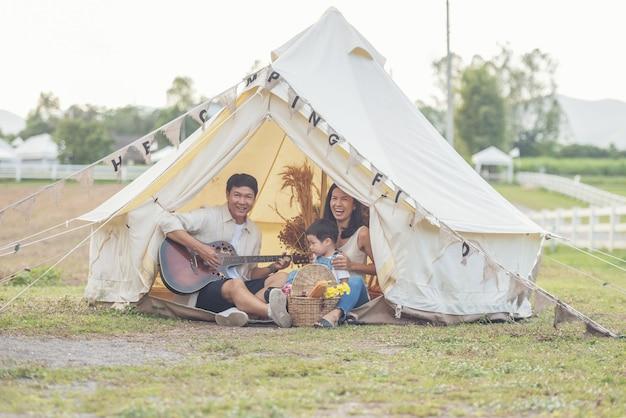Kind singt mit lächelnder familie auf dem campingplatz. familie, die campingurlaub in der landschaft genießt.