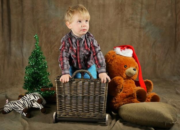 Kind sitzt am korb in der nähe von weihnachtsbaum und riesigem bären im roten hut. entzückendes kind in der nähe von geschenken. braune rustikale farben. kind bekommt weihnachtsgeschenke. weihnachtsgeschenk und neujahrskonzept.
