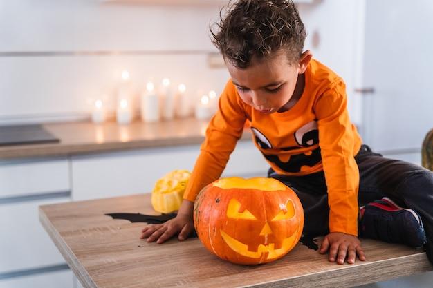 Kind sitzt am küchentisch verkleidet als kürbis und spielt mit dekoriertem halloween-kürbis-happy-hal...