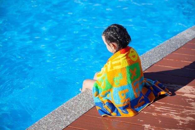Kind sitzt am pool kleines mädchen mit geflochtenen zöpfen sitzt auf der seite des pools und schaut auf das wasser...