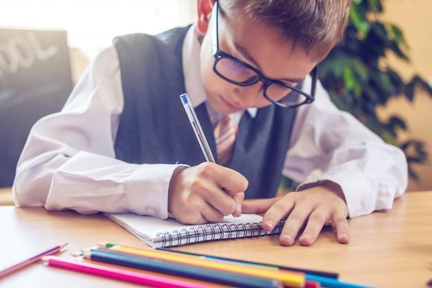Kind sitzt am schreibtisch im klassenzimmer. junge lernt lektionen schreibt einen stift in ein notizbuch