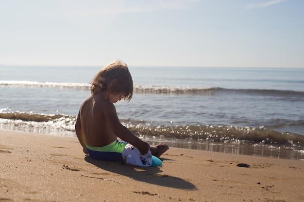 Kind sitzt am strand vor dem meer