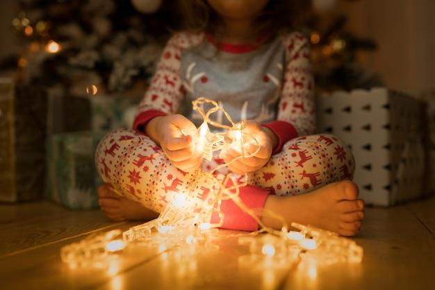 Kind sitzt am weihnachtsabend in der nähe des weihnachtsbaums und hält eine leuchtende girlande