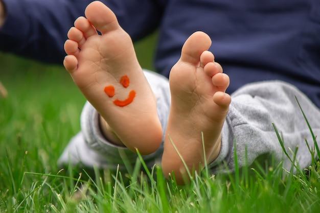 Kind sitzt auf dem gras und lächelt auf dem bein des kindes mit farbe
