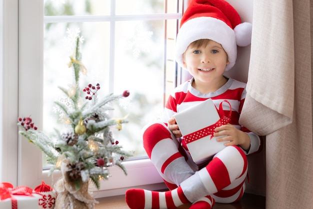 Kind sitzt auf der fensterbank glückliches kind im weihnachtspyjama