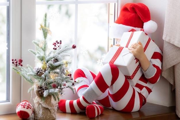 Kind sitzt auf der fensterbank glückliches kind trägt weihnachtspyjamas