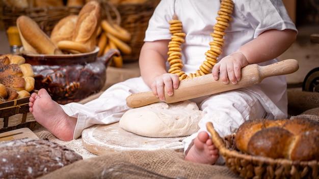 Kind sitzt auf einem holztisch und rollt den teig mit einem nudelholz aus